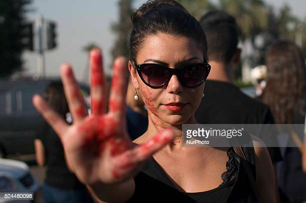 An Egyptian woman with red paint hand prints adorning on her arm takes part in a protest against sexual harasment in front of the Opera House in the...