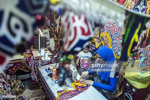 An Egyptian woman works at a workshop for traditional decoration sold during the Muslim holy month of Ramadan in the capital Cairo on June 2 2016...