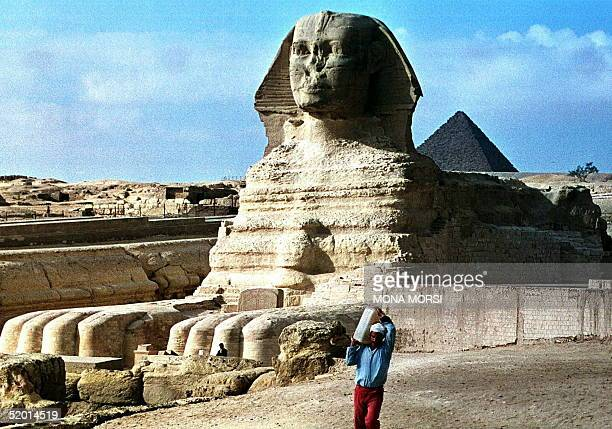 An Egyptian worker carries 28 December the last stone of the scaffolding that caged the Sphinx one of Egypt's most famous monuments The 4600yearold...