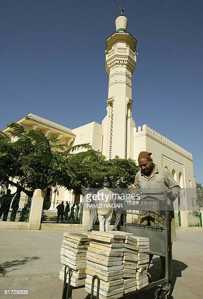An Egyptian worker transports tiles from the King Faisal Mosque close to the international airport in Cairo 11 November 2004, where Palestinian...