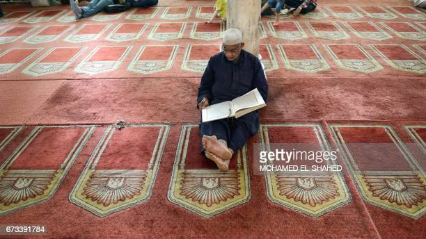 An Egyptian worshipper reads from the Koran Islam's holy book inside the 10th century historic alAzhar mosque in the capital Cairo's Islamic quarter...