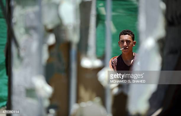 An Egyptian young boy smokes a cigarette following the demolition of the headquarters of the oncedominant party of expresident Hosni Mubarak that was...