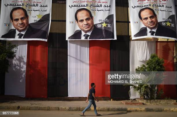 TOPSHOT An Egyptian youth walks past a polling station in the capital Cairo's western Giza district on March 25 2018 ahead of the vote scheduled to...