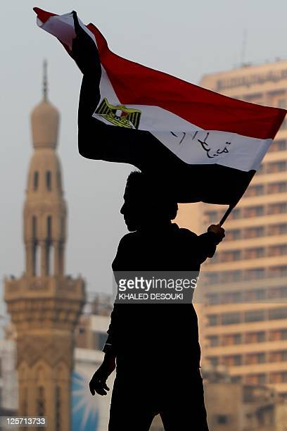 An Egyptian youth waves the national flag with slogan in Arabic that reads 25th of January Day of the Freedom following morning prays celebrating the...