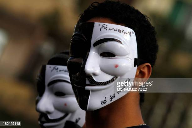An Egyptian youth wears a Guy Fawkes mask trademark of the anonymous movement and based on a character in the film V for Vendetta with writing on it...