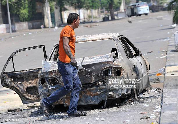 An Egyption man walks past a burnt car near Cairo University on July 23 where supporters of Egypt's deposed president Mohamed Morsi are holding an...