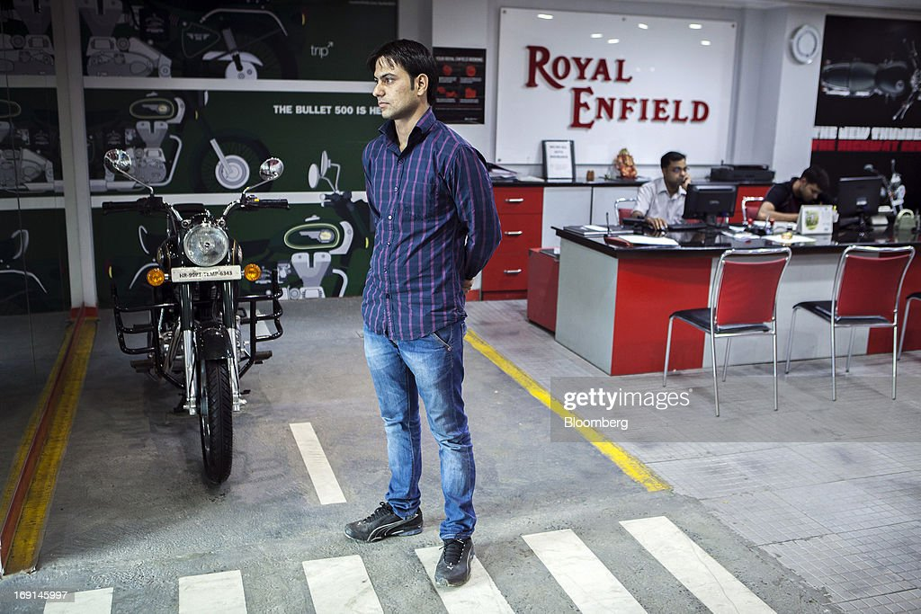 An Eicher Motors Ltd. sales assistant stands on the floor as other sales assistants work at their desks at the company's Royal Enfield flagship dealership in Gurgaon, India, on Monday, May 20, 2013. The Indian maker of Royal Enfield, the World War II-era British motorcycle owned by stars including Brad Pitt, plans to export the vehicles to Southeast Asia and Latin America as it builds on record sales at home. Photographer: Prashanth Vishwanathan/Bloomberg via Getty Images