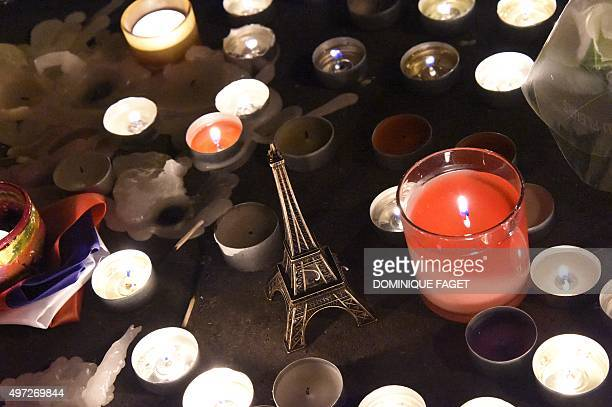 An Eiffel tower figurine is pictured among lit candles at a makeshift memorial in front of 'Le Carillon' restaurant one of the site of the attacks in...
