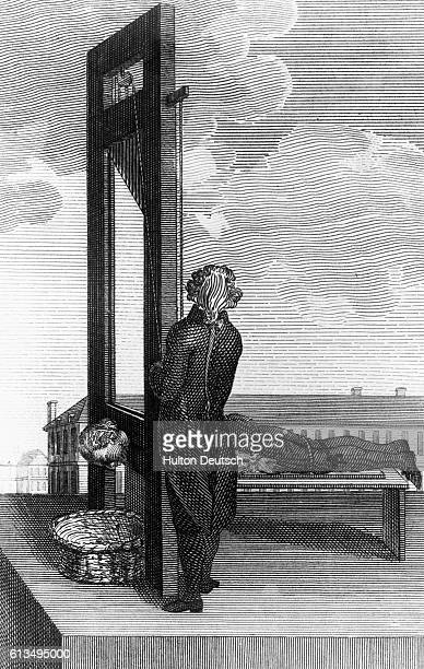 An eighteenth century etching of a guillotine execution The condemned man lies on a bench his head facing down into a basket the executioner stands...