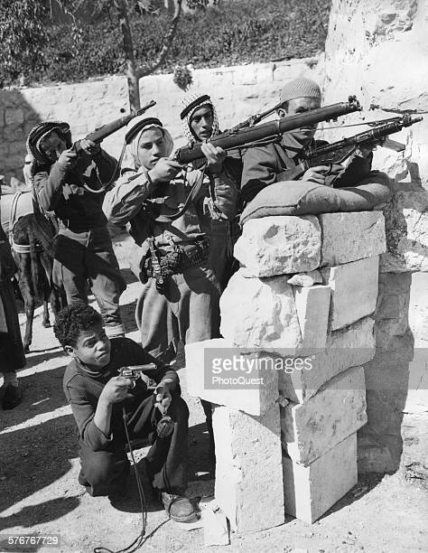 An eightyearold Arab boy joins his older brother and friends in defending the St Stephans entrance to the Old City Jerusalem March 1 1948 This boy...