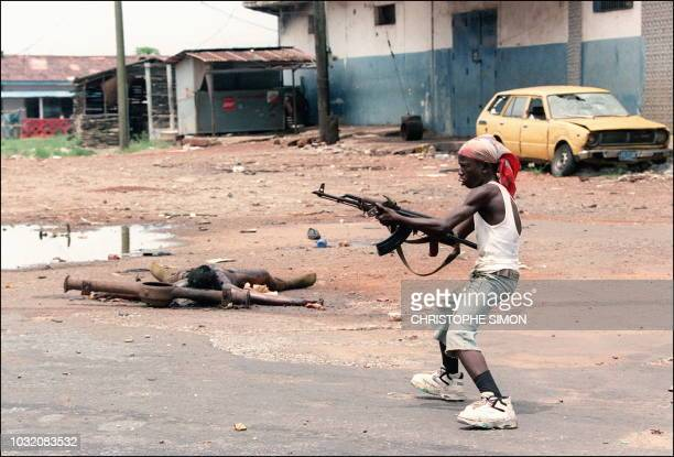 An eightyearold boy Kalashnikov gun in hand loyal to the warlord Charles Taylor chief of the National Patriotic Front of Liberia leads a group of...