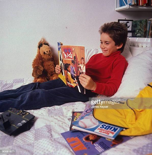 An eightyearold boy reading US KIDS magazine in bed with a stuffed ALF doll and a pile of other kids magazines by his side