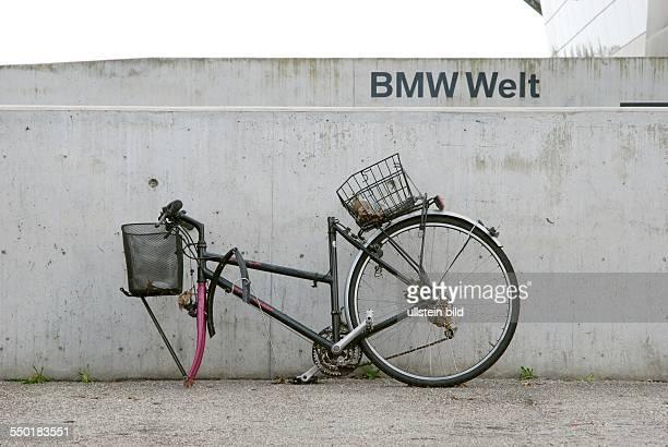 An einer Betonmauer nahe der 'BMW Welt' München steht ein demoliertes Damenrad. An dem Fahrrad fehlt das Vorderrad und der Fahrradsattel