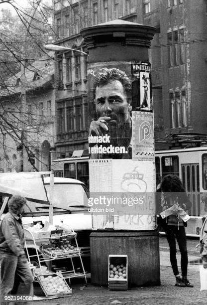 An einer Litfasssäule an der Kastanienallee Ecke Schönhauser Allee ist ein Stand mit Äpfeln aufgebaut aufgenommen im Winter 1990 Unter einem...