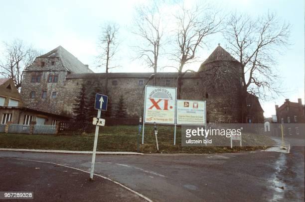 An einer tristen Straßenkreuzung vor einem historischen Bau in Harzgerode stehen zwei große Transparente mit den Aufschriften Unser Bestes zum XI...