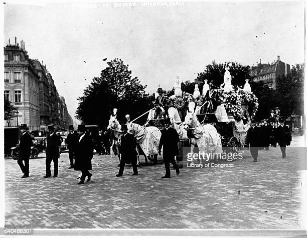 An elaborate horse drawn hearse carries the bodies of Isadora Duncan's two children through the streets of Paris May 5 1913