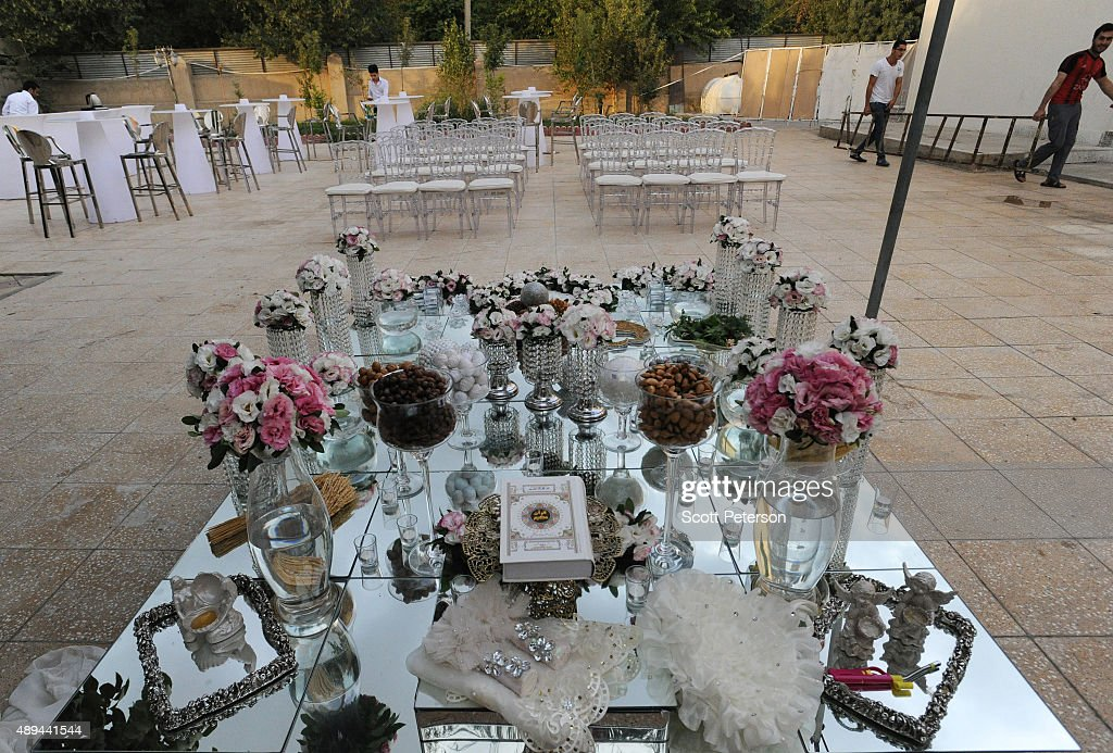 An elaborate Iranian table is laid out with flowers and glass ornaments for a luxury wedding with mixed dancing and removal of headscarves, at a private garden tailor-made for the purpose west of Tehran, Iran, on September 14, 2015. Such weddings are booming business in Iran with an average price tag of $20,000, though they also often break Islamic rules and can be shut down by police if they do not have a permit.