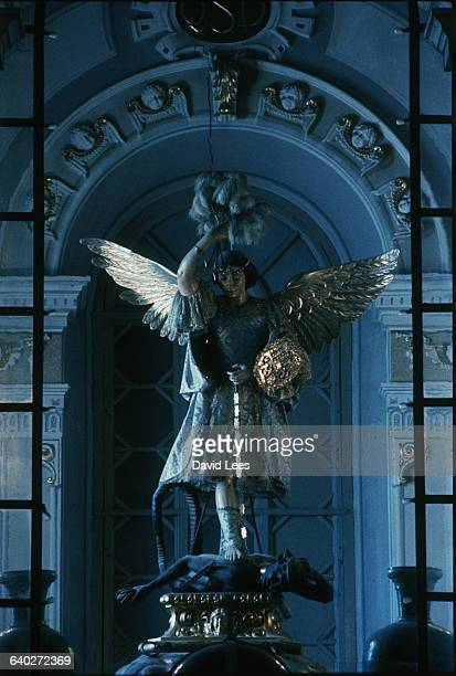 An elaborately clothed statue of Saint Michael He stands upon the black figure of Satan driving his sword into the devil's back