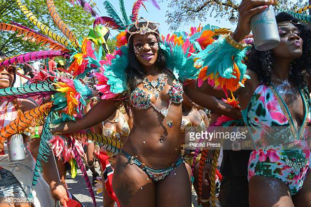An elaborately costumed dancer pauses to model her outfit Massive crowds gathered along the Eastern Parkway in Crown Heights Brooklyn to witness the...