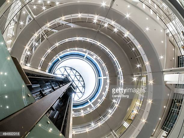 An elavator rising through a spiral staircase located in the London School of Economics.