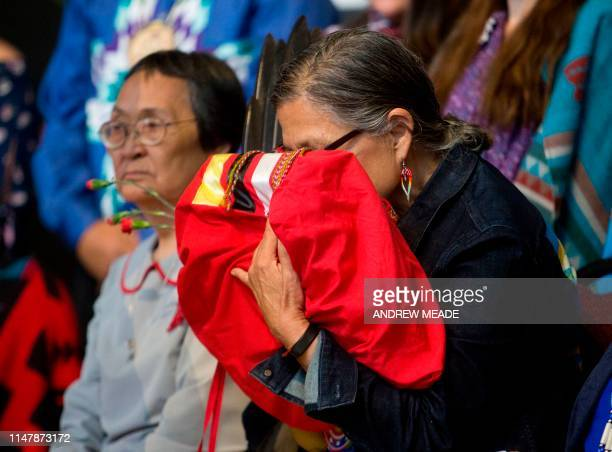 An elder indigenous women embraces the final copy of the National Inquiry into Missing and Murdered Indigenous Women and Girls at a public closing...