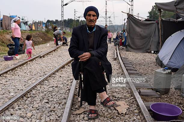 An elder Kurd refugee from Aleppo Syria sits on a cahir on the rails in the old Idomeni train station on May 1'st 2016 in Idomein refugee camp...