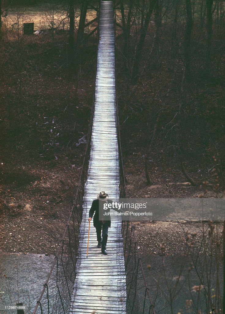 An elder man crossing a primitive rope bridge in Pike County