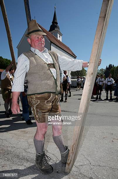 An elder man dressed in traditional Bavarian costume participate the erection of a 30 metres long maypole on May 1 in Parsberg near Miesbach Germany...