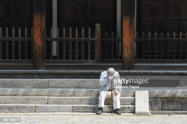CONTENT] An elder man is taking a quick nap and resting in the Toshodaiji Temple's main stairs Nara Nara Prefecture Japan The old man is wearing a...