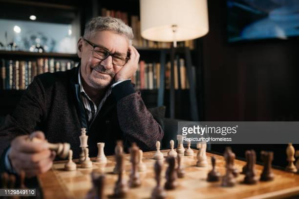 Ein älterer Mann, der Schach mit einem Lächeln spielt.