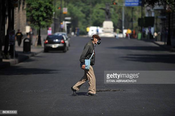 An elder man wearing a mask crosses an empty street in Mexico City's downtown on May 3 2009 The influenza A virus epidemic in Mexico is 'in phase of...