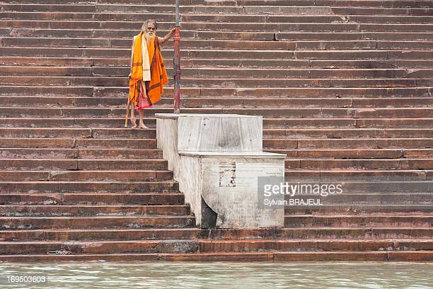An elder Naga Sadhu going down the ghat to the Ganges, opening the Royal Bath for the Sadhus, during the Maha Khumbh Mela in Haridwar, in...