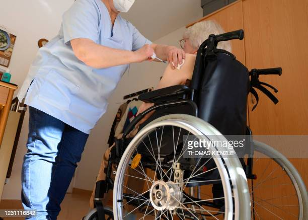 """An elder resident of the """"Geschwister Cluss"""" nursing home gets a Covid-19 vaccination in her wheelchair by a mobile vaccination team in Ludwigsburg,..."""