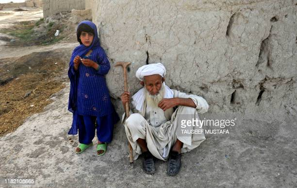 An elderly Afghan man and young girl look on as US soldiers from Bravo Troop 171 CAV Forward Operating Base Wallakan take part in a patrol in the...