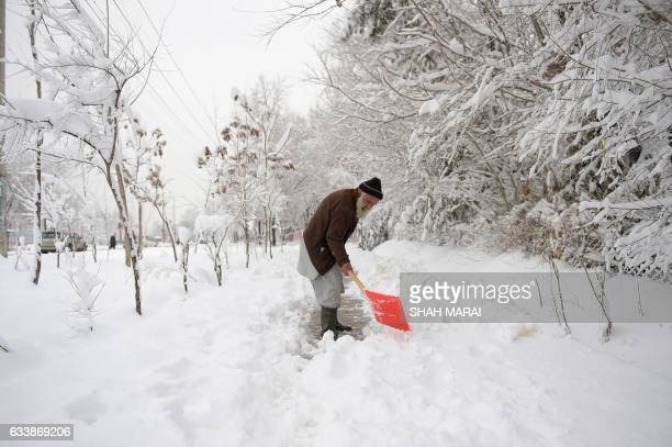 An elderly Afghan man shovels snow in Kabul on February 5 2017 Avalanches and freezing weather have killed more than 20 people in different areas of...