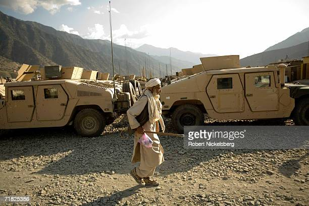 An elderly Afghan man walks through the the 10th Mountain Division motor pool at the Forward Operation Base in Naray Kunar in eastern Afghanistan on...