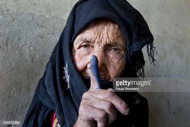 An elderly Afghan woman shows off her inked finger to the camera after she made it to the polls to cast her vote September 18 2010 in Kabul Panjshir...