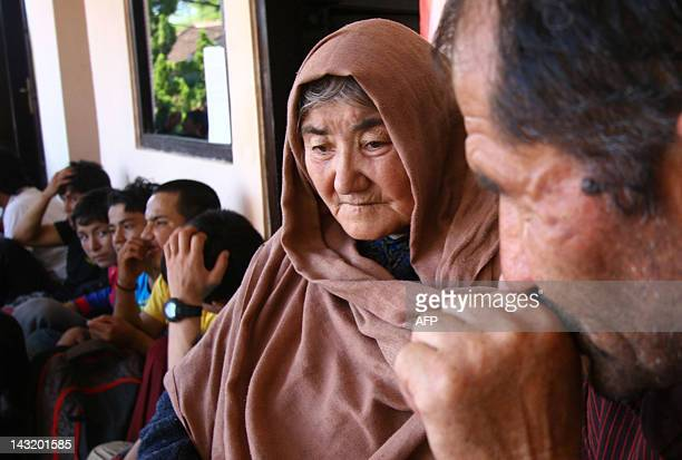 An elderly Afghan woman sits together with a group of Afghan asylum seekers at a police station in Malang town, East Java province April 21, 2012....