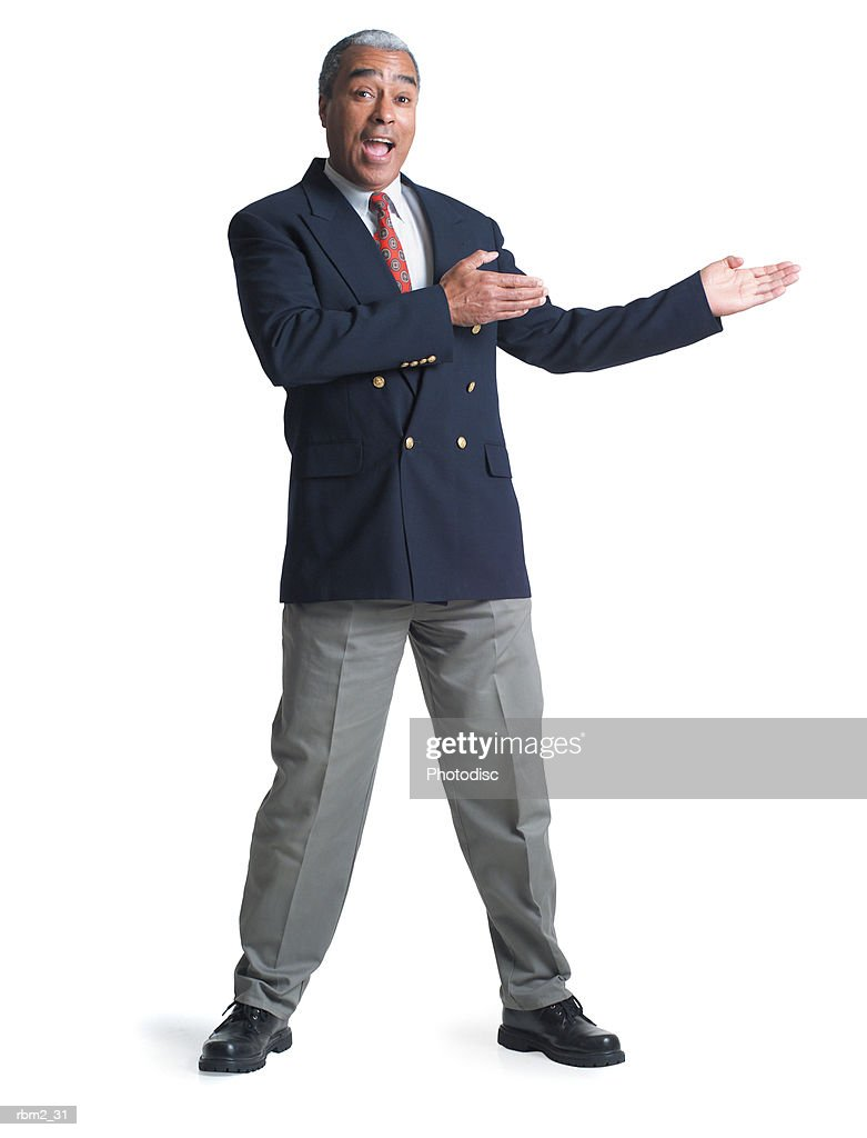 an elderly african american male in a jacket and tie gestures enthusiastically to his side : Stockfoto
