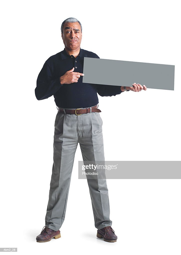 an elderly african american male in grey pants and a black shirt points to a  sign he is holding up : Stockfoto
