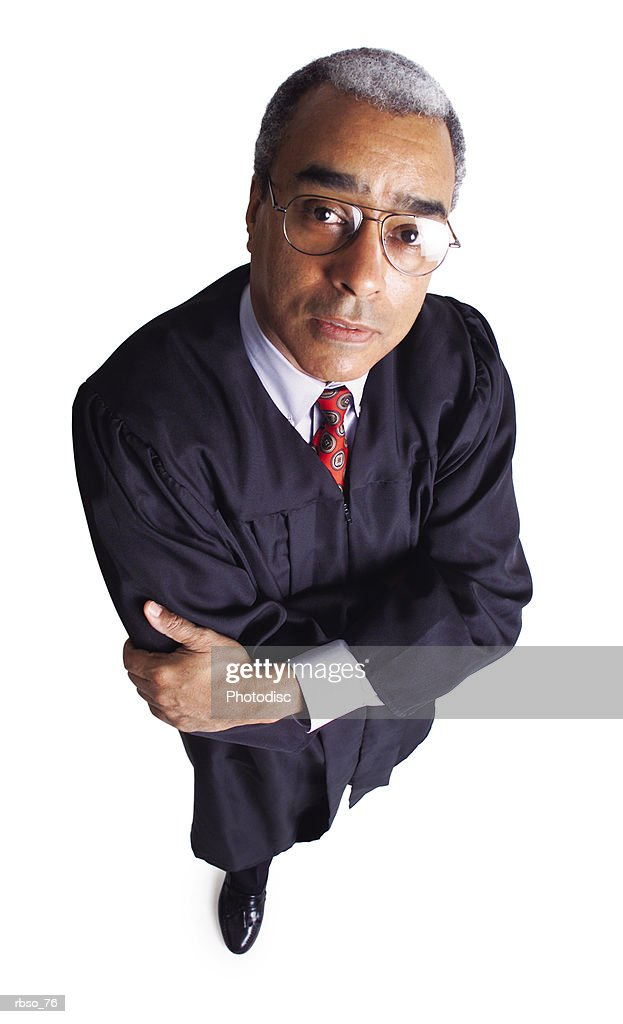 an elderly african american male judge folds his arms and looks solemnly up at the camera : Foto de stock