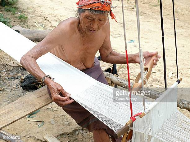 An elderly Akha ethnic minority woman weaving cotton fabric to make traditional clothing Ban Lakham Luang Namtha province Lao PDR One of the most...