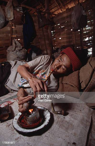 An elderly Akha man finds solace with his opium pipe at a small roadside village in Chiang Rai province northern Thailand Drug abuse remains a common...