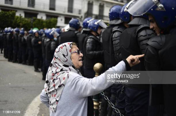 TOPSHOT An elderly Algerian woman talks to a member of the security forces cordoningoff a protest area during an antisystem demonstration in the...