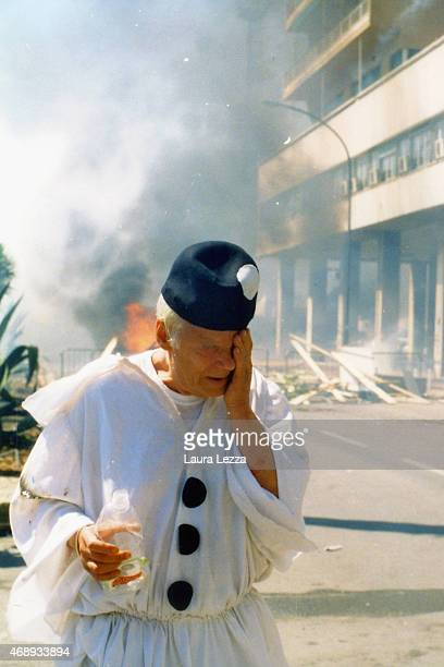 An elderly anti-G8 protester runs away during clashes with police on the second day of the G8 Summit on July 21, 2001 in Genoa, Italy. Thousands of...