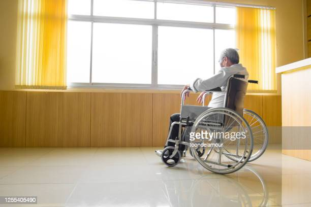 an elderly asian person is sitting on a wheelchair. - persons with disabilities stock pictures, royalty-free photos & images