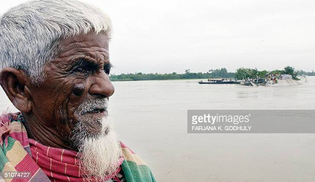An elderly Bangladeshi man looks out across flood waters at the flood affected Shimulia village subdistrict Dhunat near Bogura district some 245 kms...