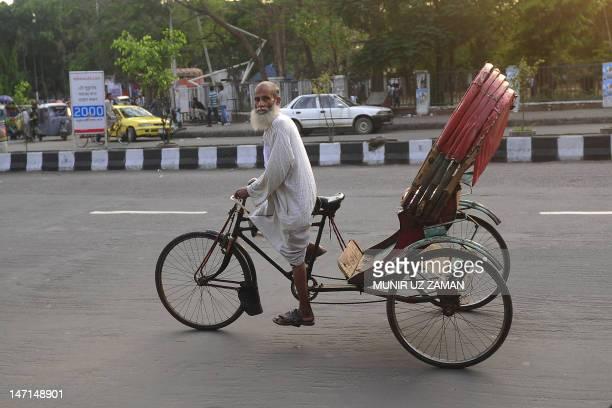 An elderly Bangladeshi rickshaw puller makes his way in Dhaka on April 10 2012 AFP PHOTO/Munir uz ZAMAN