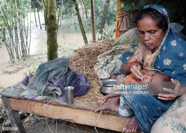 An elderly Bangladeshi woman feeds her grandson at the flood affected Shimulia village subdistrict Dhunat near Bogura district some 245 kms north of...
