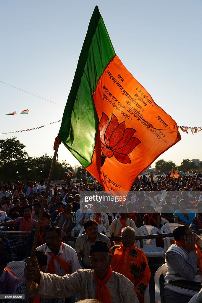 An elderly Bhartiya Janta Party (BJP) supporter (C) displays the BJP flag as he participates in a rally addressed by the Chief Minister of the western Indian state of Gujarat Narendra Modi in Ahmedabad on December 21, 2012, after his victory in state assembly elections. Indian Hindu nationalist Narendra Modi should be in a strong position to run for prime minister in 2014 after winning state polls but his own party may act to stop him, newspapers said. Modi, a hardline leader of the right-wing Bharatiya Janata Party (BJP), recorded a thumping victory in his home state of Gujarat to remain as chief minister, triggering renewed speculation about his national ambitions. AFP PHOTO/Sam PANTHAKY